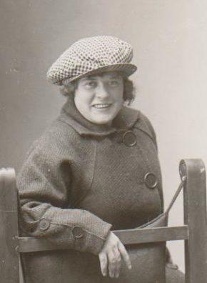 Fröken Wiström från 1915 med häftig, sportig keps. Verkar vara glad och på hugget där hon lutar sig framåt på stolen med stilenlig kappa med stora knappar som fångar ens ögon. Foto: privat