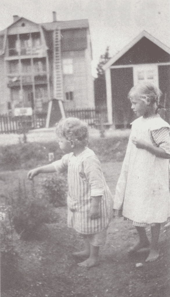 Det är år 1921 och Amerikahuset är på väg att byggas. Lille Sven Skoog är 3 år gammal och försöker fånga den något äldre Hildegard Hedströms uppmärksamhet på något spännande hemma i trädgården hos mamma Stina Skoog, Stina-på-trån som hon fick heta genom hennes arbete som telefonist. Hildegard Hedström var dotter till Julia och Håkan Hedström som på den här tiden ägde och drev Lilla Hotellet. Foto: privat