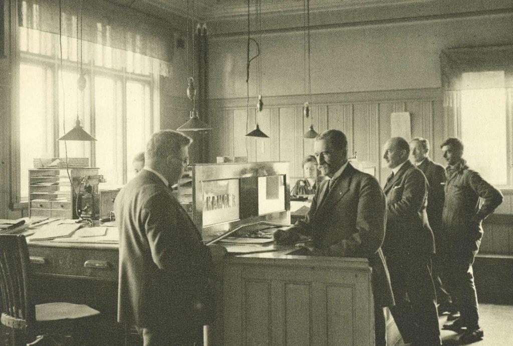 Interiör från gamla Svenska Handelsbanken med kunder och personal. Bild: Handelsbanken i Sveg