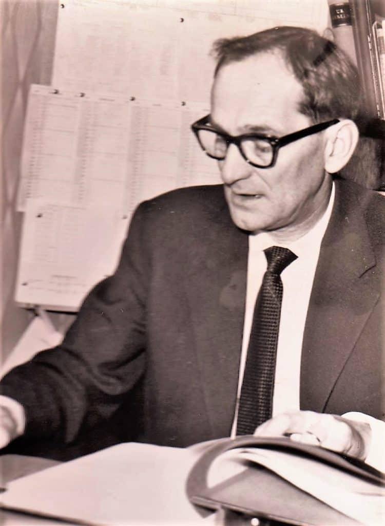 """Nils Eklund (1908-1984), rektor 1958-1968 på plats i kontoret där Maud Eriksson, rektorns högra hand skötte den löpande administrationen och lärarlönerna under åren 1963-1974. För att inte glömma skolvaktmästare Pelle Proos (1913-1993) som vi är många som minns med stort hjärta. Hjälpsam med ett lugn tills att det uppenbarade sig bus. Då kunde han slänga ut med armarna och säga """"nämen, pojkar vad har ni nu ställt till med"""" och demonstrativt ruska på huvudet """"tänk att det ska behöva vara på det här viset"""" och fick medhåll av rektor Eklund. Foto: privat"""