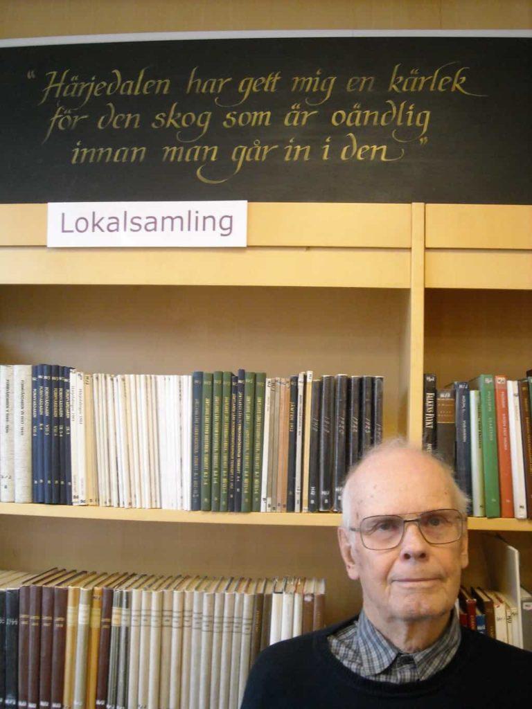 """Bo Jansson, 83 år, minns väl studierna vid Samrealskolan 1948-1952. Här framför citatet av Henning Mankell i Svegs bibliotek. Härjedalen som Bo håller varmt om hjärtat, född i Sörtjärn och uppvuxen i Sveg och många år lärare vid yrkesskolan, korrespondensgymnasiet, grundskolan och gymnasiet. Bosse, som han också kallas, är känd som """"mannen bakom kameran"""". Sedan unga år intresserad av fotografering och på äldre dagar producerat två populära foto DVD skivor, den senaste utgiven 2012, foton från Svegsbygden 1950- till 1990-tal. I det här reportaget återfinns flera av Bosses foton. Foto: Mats Haldosén"""