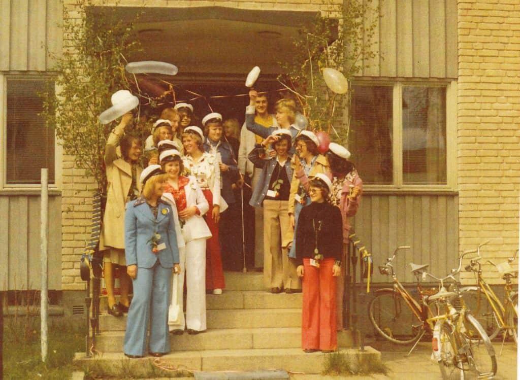 Glada och lyckliga tar gymnasisterna emot gratulationshälsningar på trappan till gamla kommunalkontoret i Sveg vars lokaler var lediga i hörnan av Härjedalsgatan och Herrögatan. Gymnasisterna blev den första årskullen som inte fick åka ner till Hermods i Malmö och ta examen. Och det var de mycket besvikna över, att inte få känna närheten till kontinenten som alla före dem hade fått göra. Slut på epoken Korrespondensgymnasiet Sveg – Hermods i Malmö. På trappan längst fram till vänster i blå dress Birgitta Persson, ovan henne till vänster i beige kappa Anita Persson och till höger i vit dress Margareta Schröder, bakom Margareta till vänster Ingalill Stenvall och till höger i röda byxor Inger Axelsson och ovan i blå kavaj Margaretha Kristoffersson och längst upp till vänster Olof Sahlin. På trappen längst fram till höger i röda långbyxor Maj-Lis Eriksson Holm, bakom henne skymtar Mariann Savgårdh och bredvid henne i beige kappa Majvor Ardbrant och Ruth Eliasson i blå kavaj som bakom sig har Ingemar Andersson och längst bak i gul skjorta Jan-Erik Nääs. Foto: Bo Jansson