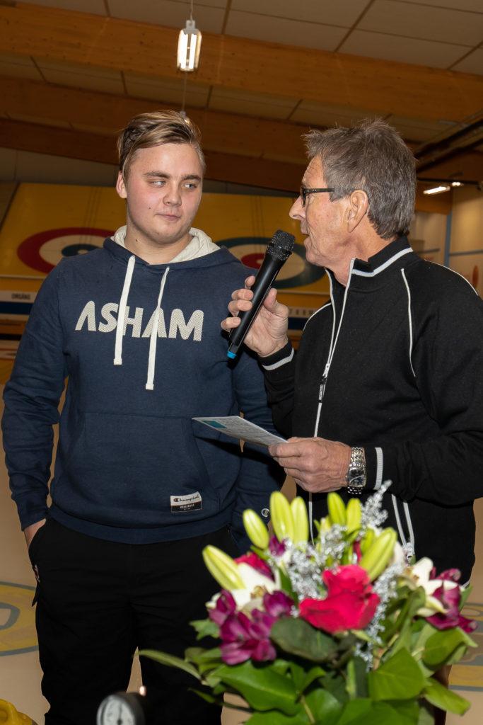 Emil Hermansson i Svegs CK/Team Berggren, uppvaktades efter sin vinst i JSM, vilket betyder att han och laget nu kommer att representera Sverige i JVM i curling i Kanada i februari. Foto: Morgan Grip