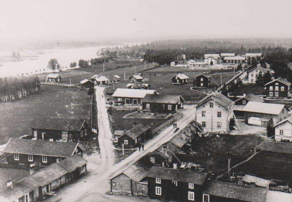 """Den ljusa fastigheten längst bort på höger sida landsvägen, två våningar och en vindsvåning med två skorstenar, är P.O. Högströms fastighet som stod färdig 1898. Huset hitom är gamla Apoteket. Fotot taget mellan åren 1898-1902. Det kan man med bestämdhet fastställa då kyrkstugorna i förgrunden på fotot brann ned på nyårsafton 1902. Foto från boken """"Älskade Sveg"""" av Mats Haldosén (1991."""