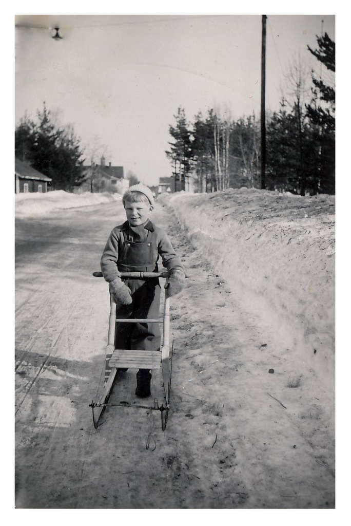 """Mats Widén som liten grabb längs Fjällvägen med sin kärt hållna vinterspark. Ett av många minnen från uppväxttiden i Sveg. Till vänster Uno Petterssons hus där Mats var dagisbarn. Där bortom ligger Johanssons hus (finns fortfarande kvar) där Per-Erik """"Snabbsnickaren"""" och hans hustru Greta bodde. Där sonen Ragnar också kom att bo med hustru Anna med barnen Siv och Gunilla. Där bakom skymtar Stora Hotellet och mitt emot på andra sidan Fjällvägen Konsums bageri. Ovan Mats hänger en tidsenlig gatlykta som präglade gatubilden i Sveg. Foto: privat"""