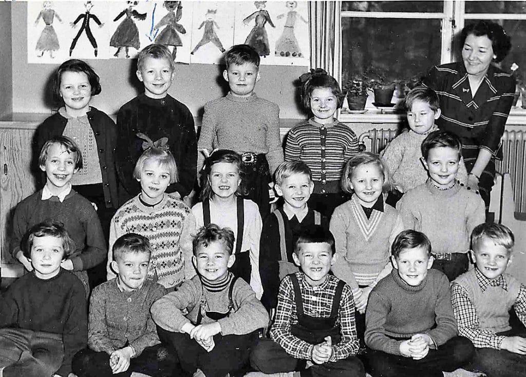 Första klass 1954 med småskollärarinnan Manda Olsson. Övre raden från vänster: Eva Maria Tallberg, Nils-Olof Bromée, Urban Hultgren, Siv Johansson och Lasse Lundh. Mellanraden från vänster: Margareta Wallén, Inga-Britt Tagesson, Margareta Wiberg, Göte Pettersson, Sara Halvarsson och Tore Wiberg. Nedre raden från vänster: Siv Hammarström, Tommy Karlsson, Christer Thornvigg, Henning Mankell, Tommy Lund och Christer Söderqvist. Manda Olsson slutade vid Norra skolan 1962 efter 41 år av anställning. Foto: privat