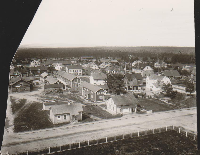 Foto från kyrktornet ner mot Småskolan (inringad) där årskurs 1-2 undervisades från 1888 med småskollärare Johanna Nygren som pionjär. Hon stannade länge i tjänsten, cirka 25 år framåt i tiden. Innan Småskolan var fastigheten så kallad sockenstuga där kommunalstämmorna hölls. Huset revs 1968. Huset till höger på fotot är familjen Anton Svenssons hus och där bakom i det tvärställda avlånga huset låg den flitigt besökta Anton Svenssons biograf med stumfilmer som ackompanjerades till piano. Foto: privat