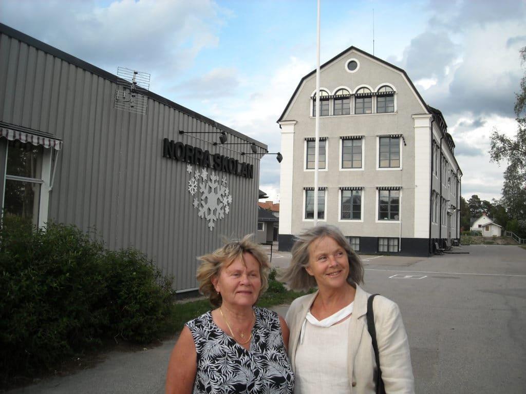 Ewa Klockervold och Gunilla Lagercrantz med den gamla skolbyggnaden i bakgrunden som fått sin ursprungliga ljusgrå fasad tillbaka efter att under en mellanperiod varit belagd med röd färg och en entrédörr i härligt blått. Foto: Mats Haldosén