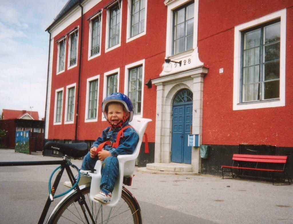 Lille Joel Haldosén, 2 år, på besök vid Norra Skolan 1994 som han gillade skarpt. Saknar idag den blå dörren och röda fasadfärgen som påminner om Pippi Långstrump färger. Foto: Pappa Mats