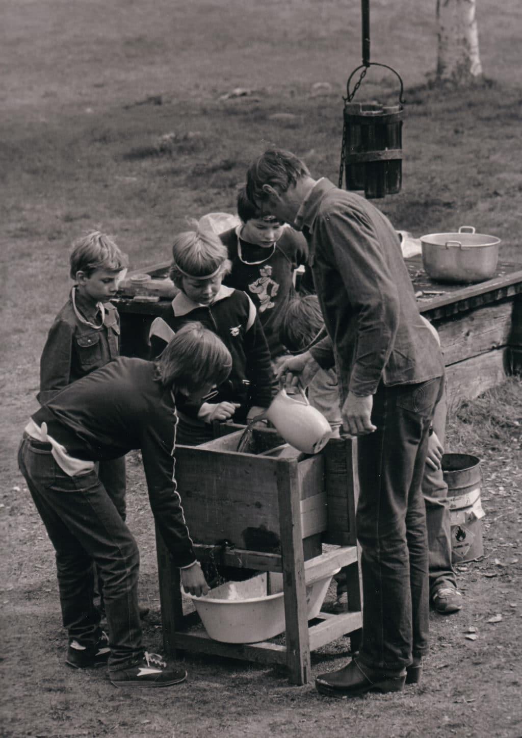"""En populär och årligen återkommande utflykt var Gammelgården där eleverna fick vara med om en """"tidsresa"""" i sällskap med Hans """"Hans Ersa"""" Eriksson (1928-2017), nestor på området Gammelgårdens historia. Här undervisar han skolelever i konsten att göra potatismjöl. Skala råpotatis som sköljs i vatten som sedan mals ner i en speciell kvarn för att stå i vatten i ett dygn så att potatismjölet fälls ut. Levande historia när den är som bäst. Foto från jubileumsboken Svegs Hembygdsgård 100 år, Mats Haldosén 2013."""