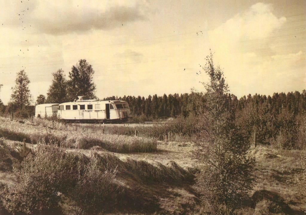 Hilding Carlssons populära tvåaxliga rälsbuss med släp som blev en stor succé. Tillverkad 1935 i över 60 exemplar. Här på väg mot Orsa nedan bondgården i Bäckedal vid tiden före invigningen av Bäckedals folkhögskola 1954. Foto: Gunnar Fåhreus City Foto i Sveg