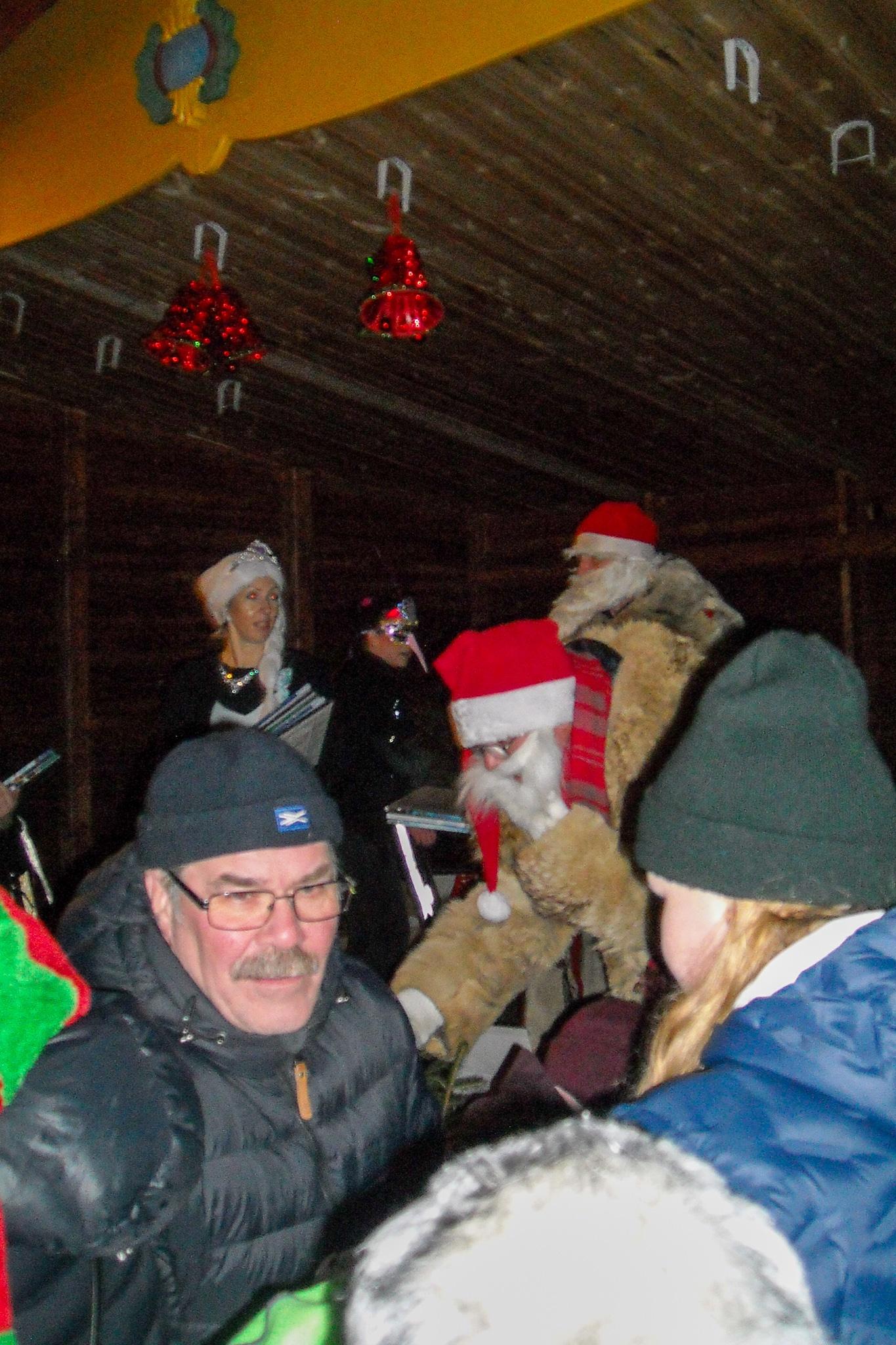 Tomtarna i full färd med att dela ut julklappar till barnen som blev rena anstormningen. Så pressat så att en av åskådarna tyckte att det var nog lika bra att fly fältet medan tid är. Foto: Mats Haldosén