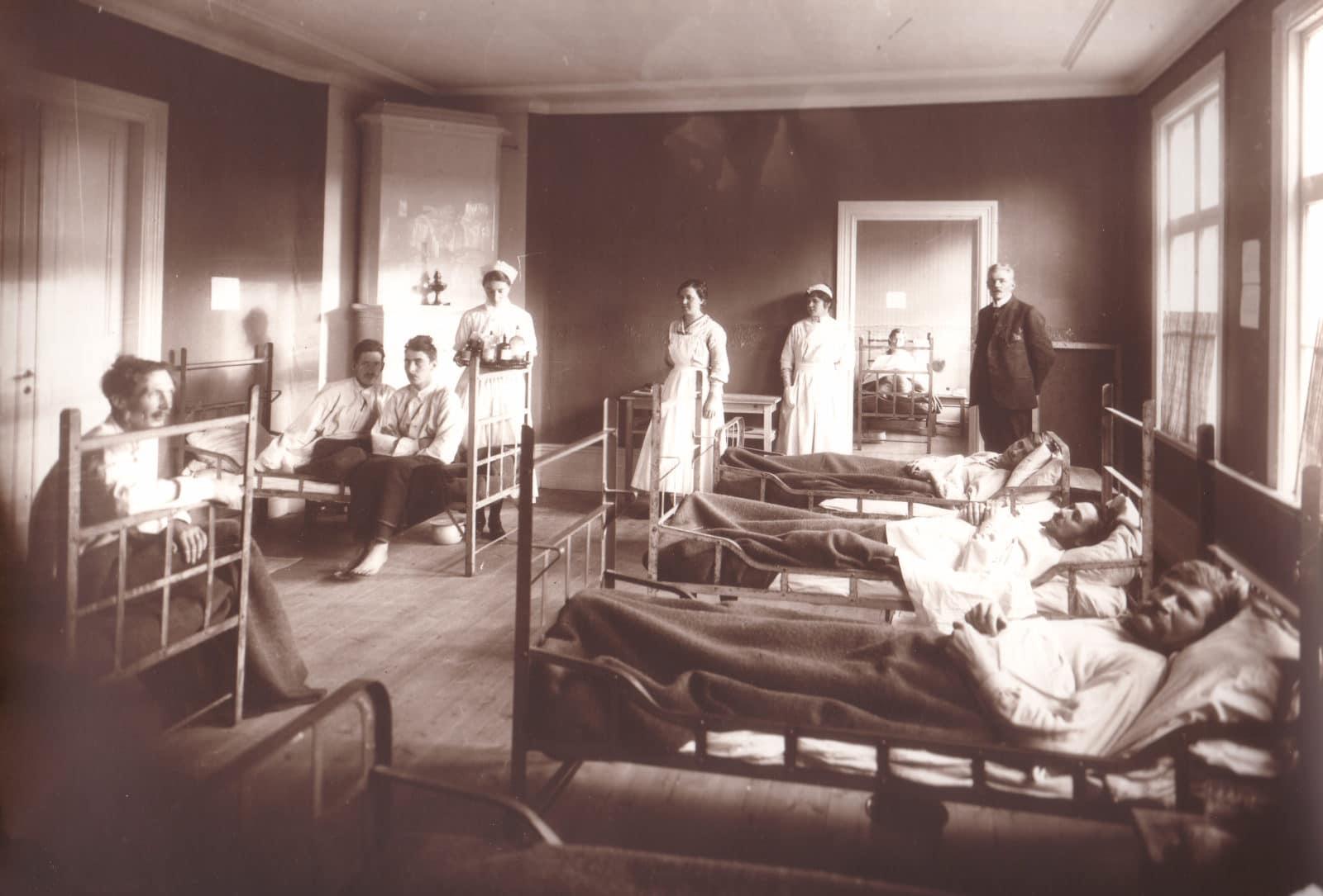 """Svegs sjukstuga, föregångaren till Svegs länslasarett, bedrev här sjukvård 1901-1933. Här överfylld av patienter drabbade av Spanska sjukan 1918-1920 med doktor Oskar Ludvig Svenonius i bakgrunden med sjuksyster och biträden. Till råga på allt under det dramatiska året 1918 lades även patienter in med difteri som var en annan epidemisjukdom (annan benämning äkta krupp) som drabbade närmare 28 000 personer i Sverige. Fastigheten till sjukstugan finns kvar, adress Ögränd. Mer om Svegs sjukstuga finns att läsa i boken """"Härjedalingarna, sjukvården och hälsoarbetet 1924-2014"""" av undertecknad."""
